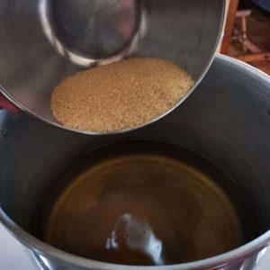 Versez le vin dans une bassine, ajoutez le sucre et mélangez afin de bien le dissoudre.
